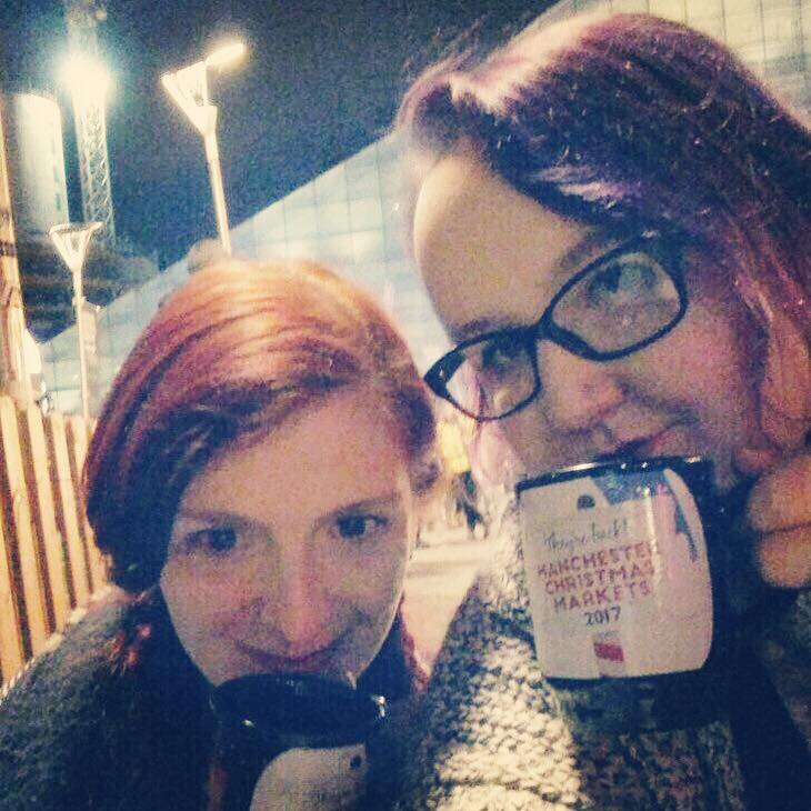 Rachel and Caroline face the camera in a slightly dark outdoor setting. They are both holding mugs from Manchester's Christmas markets in 2017. Caroline's hair is purple in this photo