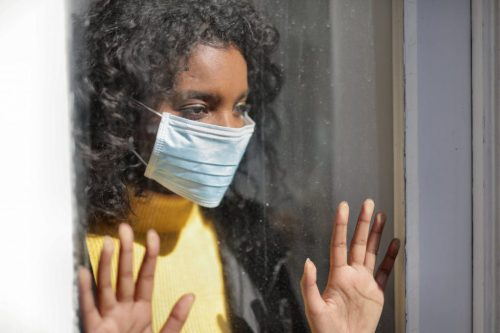 Black woman with black hair in a blue surgical mask pressing her hands on a window
