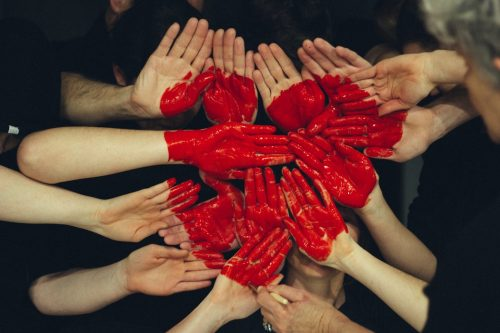 a group of white hands all coming together and half painted red to create a big heart