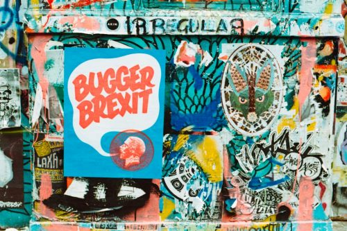 """A wall of graffiti, one piece is a blue background with the words """"Bugger Brexit"""" in red"""
