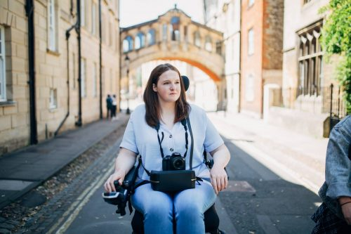 A white woman with brown hair in a powerchair, looking off to the side behind the camera. She has a digital camera around her neck. The background is a street/road with a nice arch