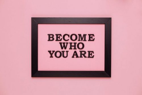 "A pink background with the words ""Become Who You Are"" in black, surrounded by a black frame"