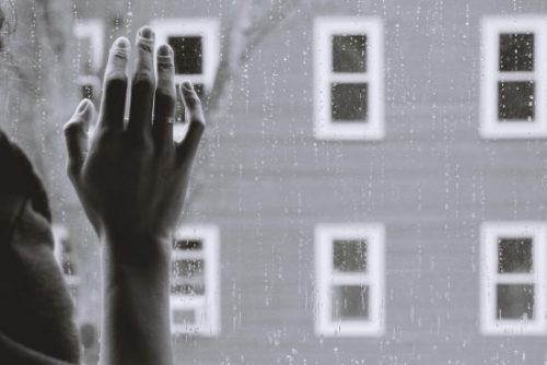 The hand and part of the shoulder of a white person taken from behind, the hand is resting on a window. Outside there is a building and a tree, and it is raining
