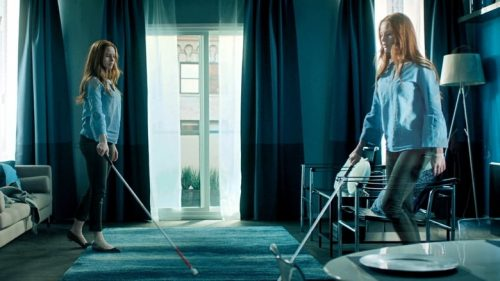 Still from image Sightless, showing character Ellen in her flat in a montage-like scene, she is using her white cane