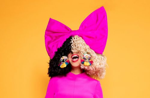 "Recording artist Sia - press for movie ""Music"" - She is in pink with a big pink bow on her head, her half black and half white wig covers half of her face"
