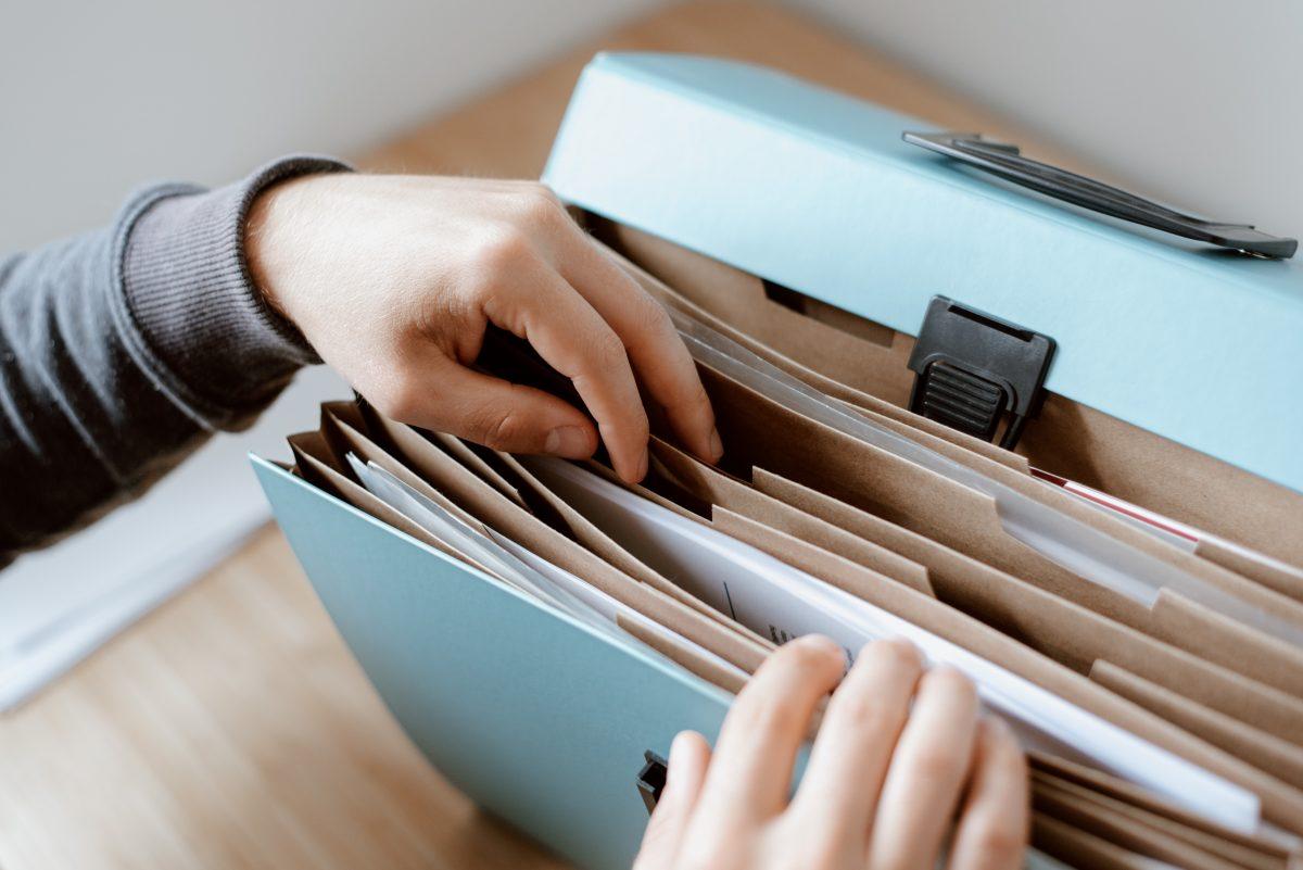 White hands rifling through a blue expanding box file