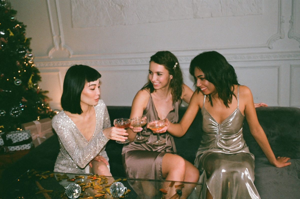 Three feminine presenting people, all dressed up, sitting down in a bar/club and cheers-ing with cocktails