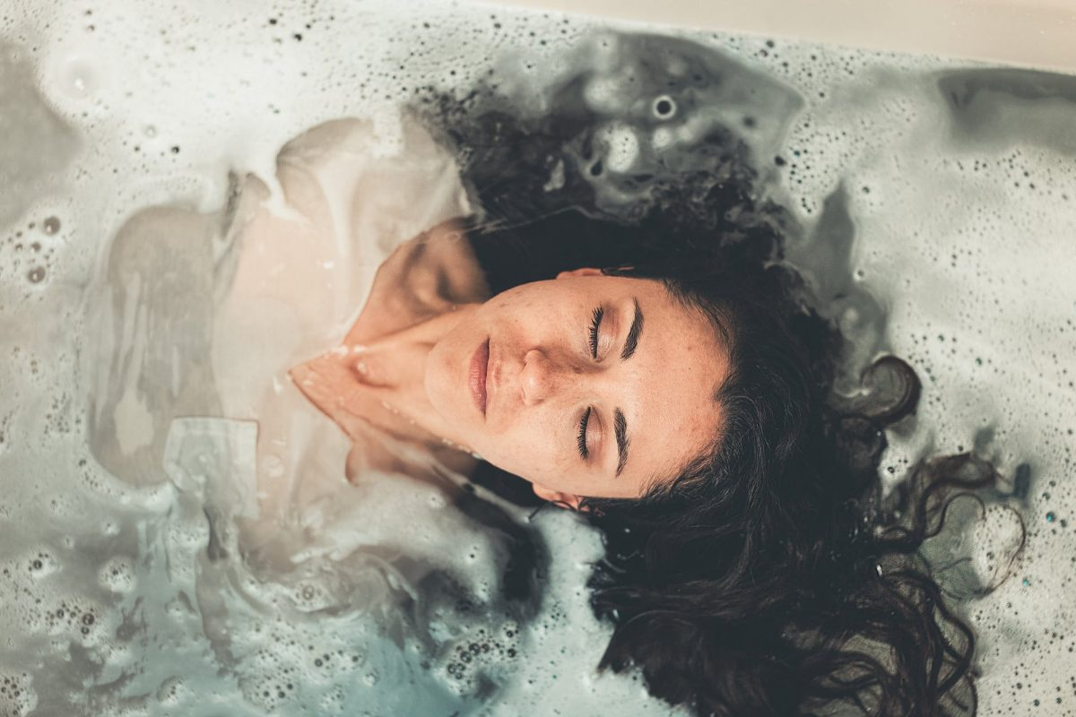White woman with dark hair dressed in a white dress in a bathtub full of water. Her eyes are closed