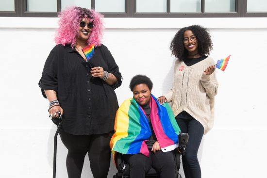 Three disabled people, one is draped in a pride flag, the other two holding pride flags