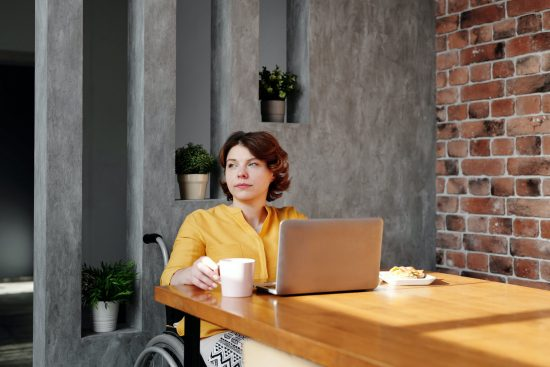 White woman in wheelchair sits at a computer with a coffee and looks into distance