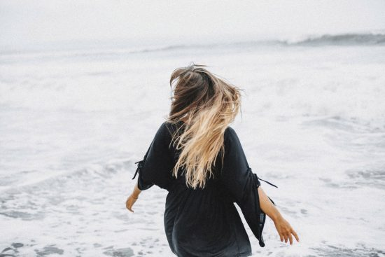White woman facing the sea, arms out as if spinning around