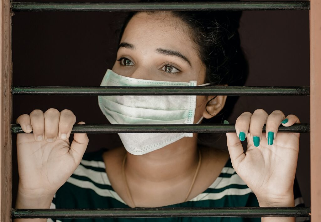 Woman in white mask holding bars on a window