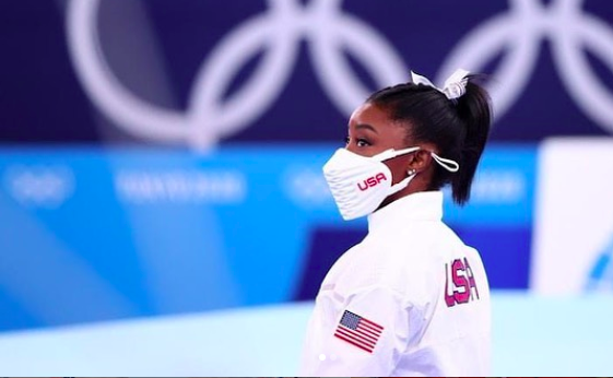 Simone Biles (black woman with dark brown hair) stood beneath Olympic rings and wearing a mask