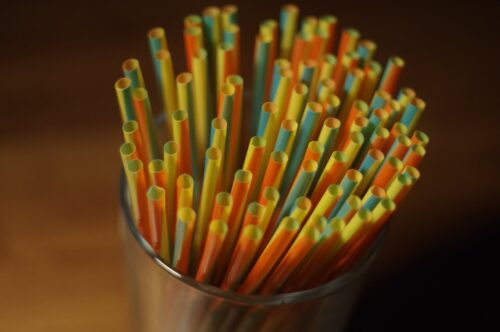a container of colourful plastic straws