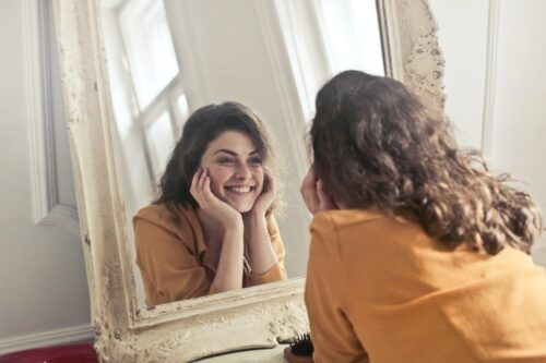 A white woman with brown curly hair looking at her reflection in the mirror and smiling