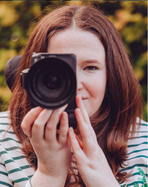 a white woman with brown hair holding a camera up to her face